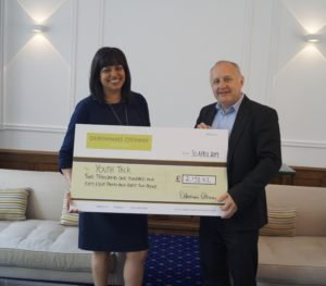 Susan Glenholme and David Barker holding a large cheque Youth Talk